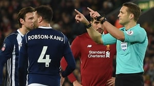 Referee Craig Pawson indicates he's going to the VAR at Anfield
