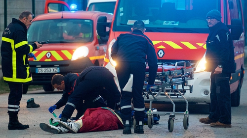 A man receives medical attention following clashes near the ferry port in Calais