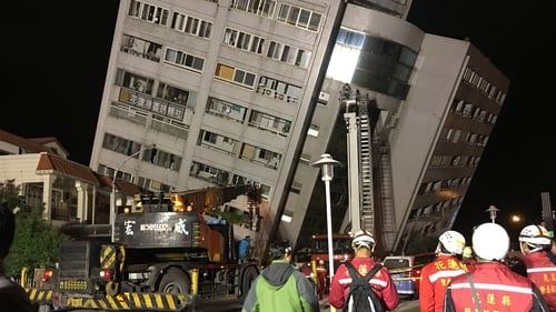 Rescue workers block off the area to search for survivors outside a building after its foundation collapsed in Hualien