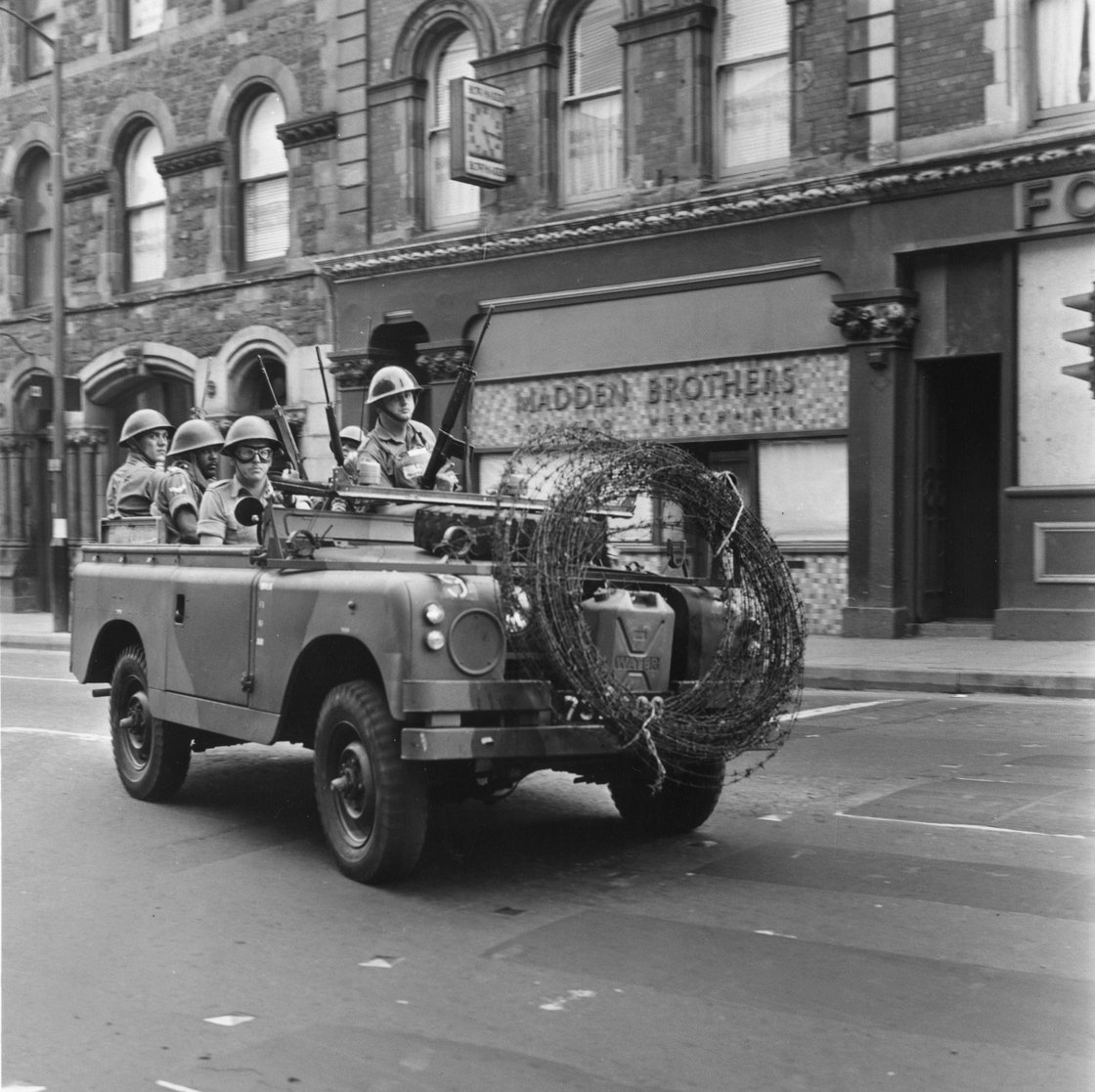 Image - Armed British soldiers driving through Derry City on a mobile patrol, 1969