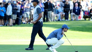 Rory McIlroy (R) lines up a putt on the 14th green beside Tiger Woods