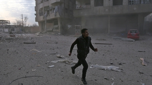 A Syrian man runs in a street  following a reported regime air strike in the rebel-held town of Hamouria, in eastern Ghouta