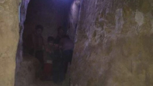 A family huddles in a bomb shelter in Eastern Ghouta (Pic: Women Now)