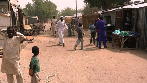 Residents walk along a street in Dapchi, Nigeria