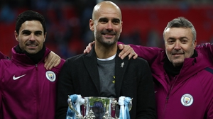 Pep Guardiola poses with the trophy alongside assistants Mikel Arteta (L) and Domenec Torren