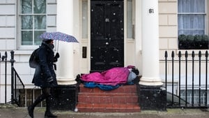 A woman walks past a homeless person sleeping in a doorway during a snow shower in London today