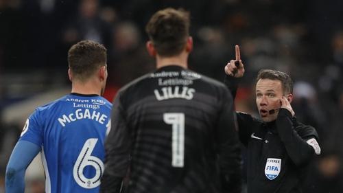 Referee Paul Tierney (r) listens to VAR decision to disallow Erik Lamela's goal