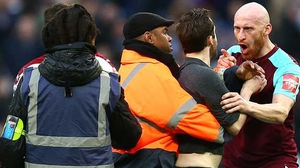 James Collins of West Ham United confronts a pitch invader