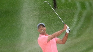 Tiger Woods plays a shot from a bunker on the first