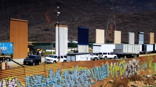The prototypes tower over the existing graffiti-covered border fence near hills on the edge of San Diego