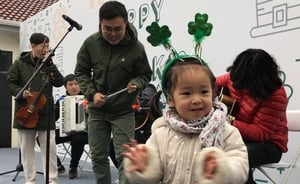 A little girl enjoys the traditional music at the Saint Patrick's Open Day at the Embassy of Ireland in Beijing, China