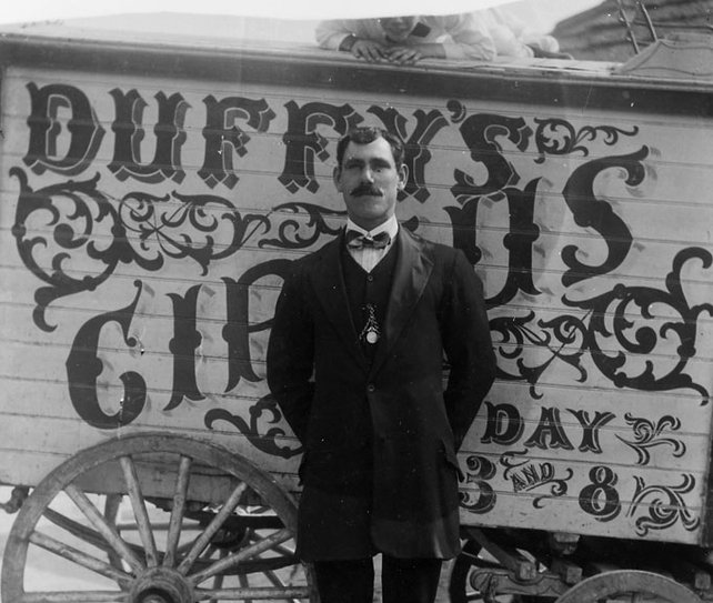 Ed123-Duffys-Circus,-man-standing-in-front-of-a-wagon-labelled,-Duffys-Circus-c19