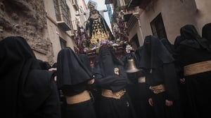 Penitents of 'Santa Cruz' brotherhood rest as they take part in a procession in Malaga