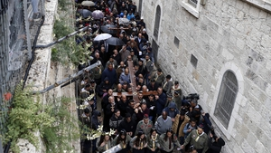 Christian pilgrims carry a large wooden cross along the Via Dolorosa (Way of Suffering) in Jerusalem's Old City