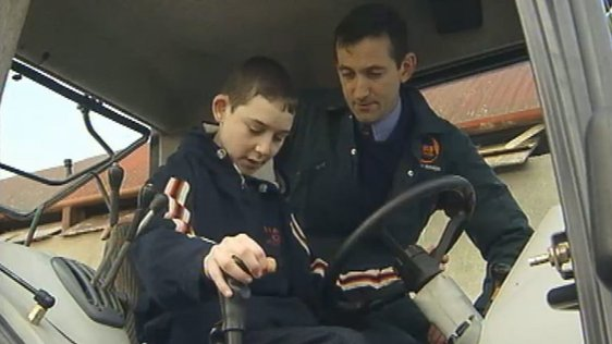Jim Dockery teaching teenager how to drive a tractor (2003)