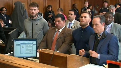 Conor McGregor (third from left) and fellow fighter Cian Cowley (far left) in court today
