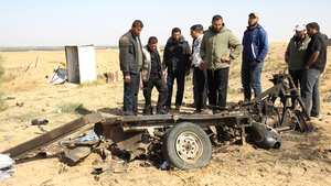 Palestinian men look at the debris of a motorcycle at the site of an explosion in east of Rafah