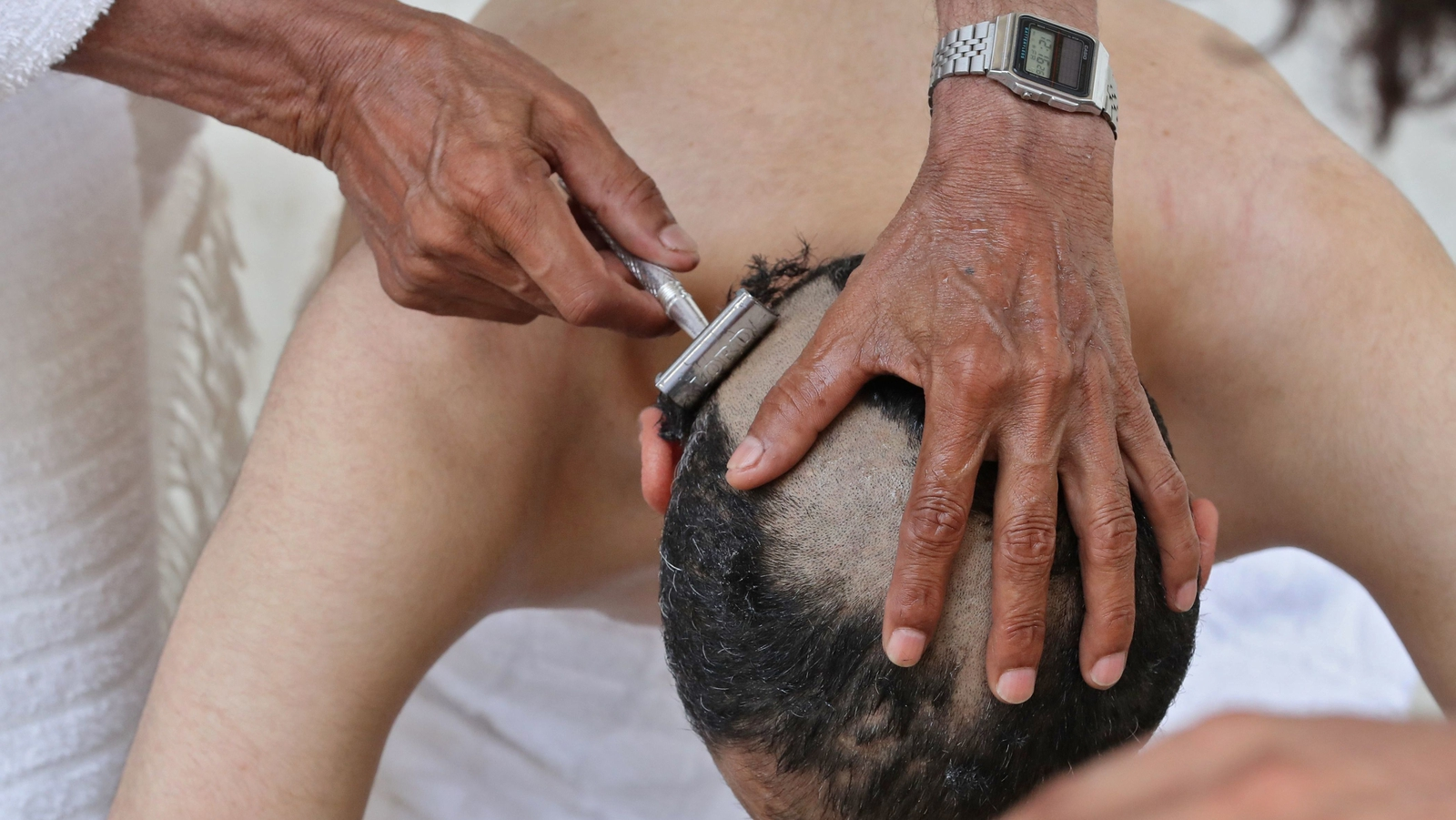 Image - A Muslim pilgrim is shaven after pebbles thrown at pillars during the symbolic stoning of the devil