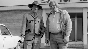 Broadcaster Donncha Ó Dúlaing (left) with Irish country music singer Big Tom, outside the latter's recording studio in the town of Castleblayney, County Monaghan, during the filming of RTÉ Television's 'Donncha's Travelling Roadshow' in March 1980.
