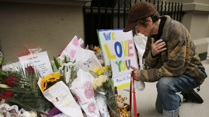 A woman lays flowers outside the Manhattan apartment where Lucia and Leo Krim were stabbed to death in 2012