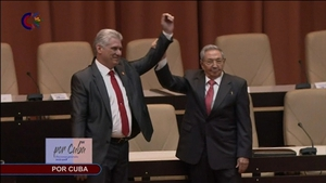 Outgoing Cuban President Raul Castro (right) raises the hand of incoming president Miguel-Diaz Canel