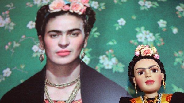 A Frida Kahlo doll is seen next to a picture of the Mexican artist