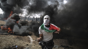 Palestinian protesters threw rocks and burned tyres near the Gaza-Israel border today