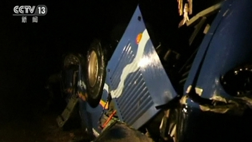 Chinese media showed images of a crashed blue bus with its wheels in the air, in footage taken in pouring rain in the dark