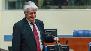 Radovan Karadzic arrives in a courtroom before the International Residual Mechanism for Criminal Tribunals