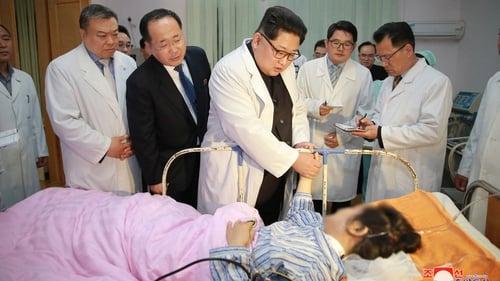 North Korean President Kim Jong-un (C), visiting a victim of the bus crash
