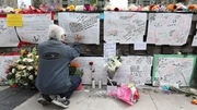 A man leaves a notes at a makeshift memorial for the victims in Toronto