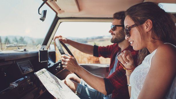 Young couple using a map on a roadtrip for directions