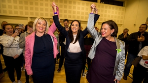 Michelle O'Neill (left) and Mary Lou McDonald raise the arms of Órfhlaith Begley as the newly-elected Sinn Féin MP for West Tyrone