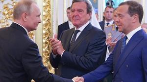 Russian President Vladimir Putin shakes hands with Russian Prime Minister Dmitry Medvedev