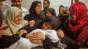 The mother of Leila al-Ghandour, the baby who died from tear gas inhalation, holds her at the morgue in Gaza
