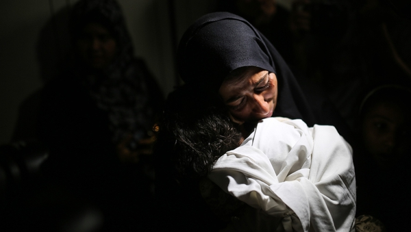 The mother of Leila al-Ghandour, the baby who died from tear gas inhalation, holds her at the morgue in Gaza. Photo: Getty Images