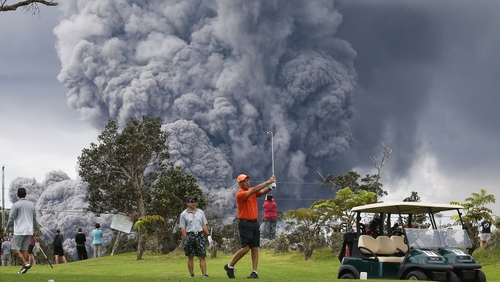 People play golf as an ash plume rises in the distance from the Kilauea volcano on Hawaii's Big Island
