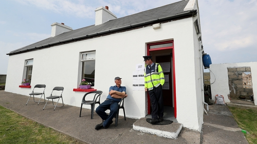 A resident of Gola Island speaks to a garda as he waits to cast his vote in his home which has been turned into a polling station for the day