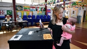 Niamh Gavin, holding her daughter Fiadh, casts her vote at St Paul's National School in Athlone