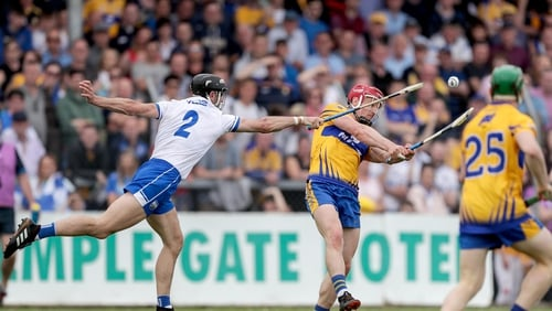 Clare's John Conlon scores a point despite the attention of Shane Fives