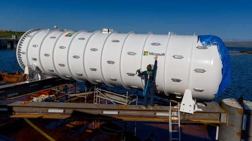 Spencer Fowers, senior technical staff member  of Microsoft's special projects research group, seals a logo onto Project Natick's Northern Isles datacenter in preparation for deployment near Scotland's Orkney Islands.