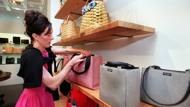 Designer Kate Spade tidies up a display of women's handbags at her new store on Newbury Street in Boston