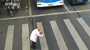 The man, who had two walking sticks, was shuffling across a road with six lanes in Mianyang city