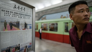 A displayed North Korean newspaper on the Pyongyang subway showing images of  leader Kim Jong-un in Singapore ahead of his meeting with US president Donald Trump