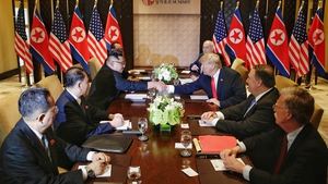 US President Donald Trump and North Korea's leader Kim Jong Un shake hands as they sit down with their delegations for the US-North Korea summit at the Capella Hotel in Singapore