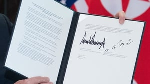 Donald Trump holds up a document signed by him and  Kim Jong-un following a signing ceremony during their summit