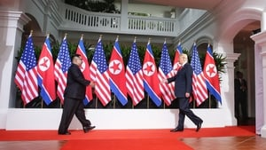 In this handout photo, Kim Jong-un (L) and US President Donald Trump approach each other for their first meeting