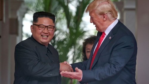 Kim Jong-un and Donald Trump smile after shaking hands at the start of their summit