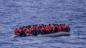 People on a rubber boat off the coast of Libya await rescue