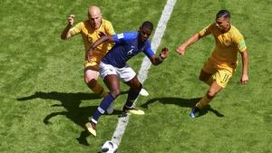 France's midfielder Paul Pogba (C) dribbles past Australia's forward Andrew Nabbout (R) and Australia's midfielder Aaron Mooy